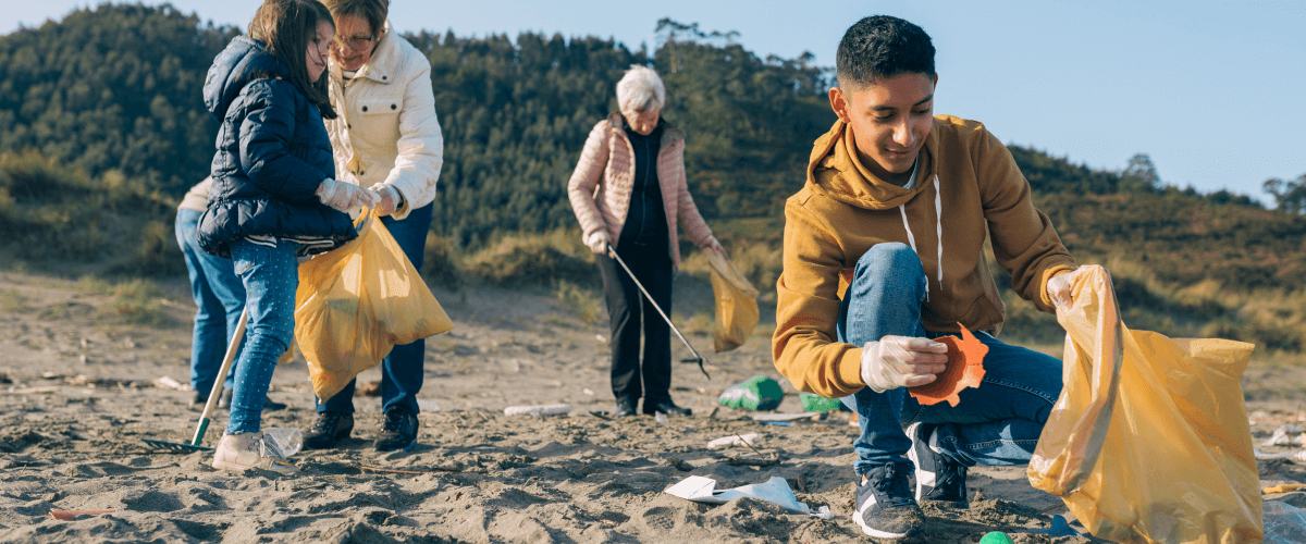 Five people collect garbage on a beach. A teenage boy crouches to pick up plastic.
